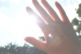 光が眩しくて手で遮る